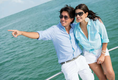 yacht people: Summer couple sailing in a yacht and pointing away Stock Photo