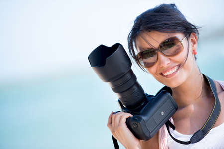digital camera: Professional female photographer holding a camera and smiling