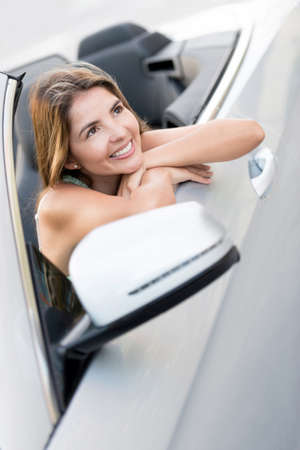 Beautiful woman daydreaming in a car and smiling photo