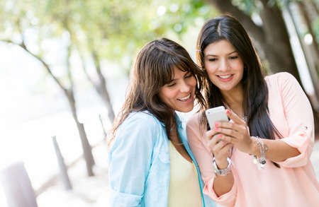 Women using a smart phone outdoors looking very happy photo