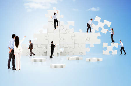 puzzles: Business teamwork in action creating a puzzle on the cloud Stock Photo