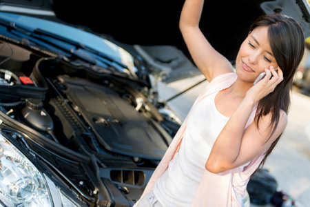 Woman with damaged car looking under the hood and making a call photo