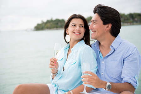 Couple drinking champagne outdoors enjoying their summer holidays photo
