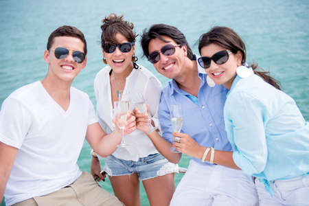 Group of friends enjoying the summer drinking champagne and sailing photo