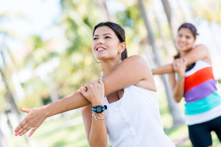 Athletic women stretching her arms at the park photo