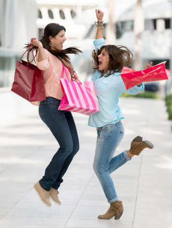 Excited shopping women jumping and holding bags photo