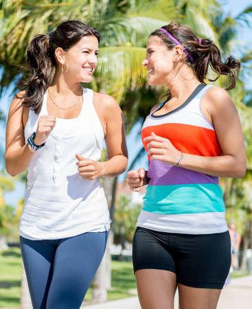 mujeres corriendo: Mujer hermosa del ajuste que correr al aire libre y una mirada feliz Foto de archivo