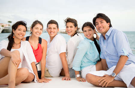 Happy group of friends on a boat enjoying the summer photo
