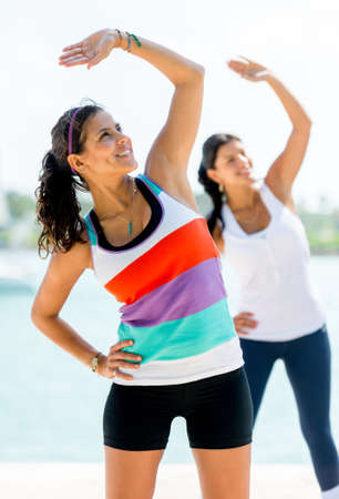 woman exercising: Beautiful women exercising outdoors stretching their arms Stock Photo