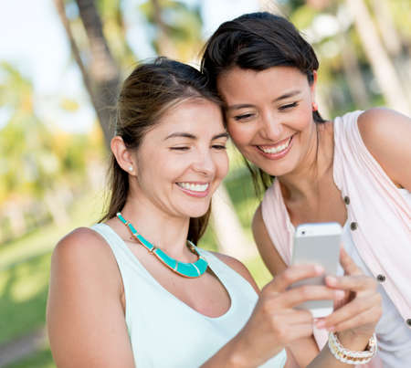 send sms: Happy girls using app on a mobile phone Stock Photo