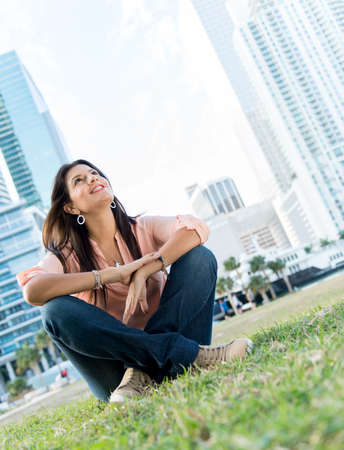 woman looking up: Beautiful thoughtful woman sitting at the park and smiling
