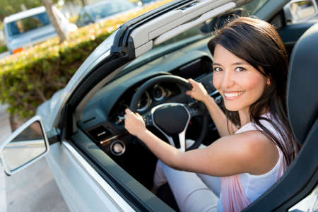 woman driving car: Female driver looking very happy driving a car Stock Photo