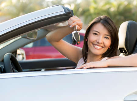Happy woman holding keys of a car and smiling photo