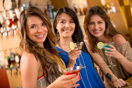 Beautiful group of girls having drinks at the bar and smiling photo