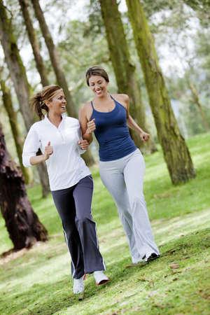 mujeres corriendo: Mujeres correr al aire libre en el bosque buscando feliz Foto de archivo