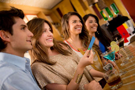Group of people paying for drinks at the bar and smiling photo