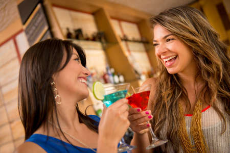 Two women having drinks at the bar looking very happy photo