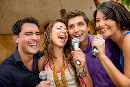 gente cantando: Grupo de amigos que se divierten cantando karaoke en el bar