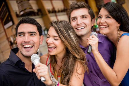 Group of people karaoke singing at a bar having fun photo