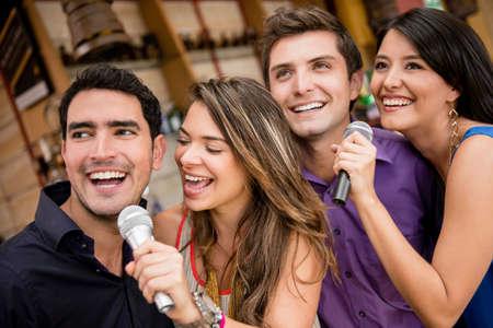 personas cantando: Grupo de gente cantando karaoke en un bar de la diversi�n