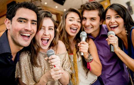persona cantando: Grupo de amigos cantando karaoke en el bar Foto de archivo