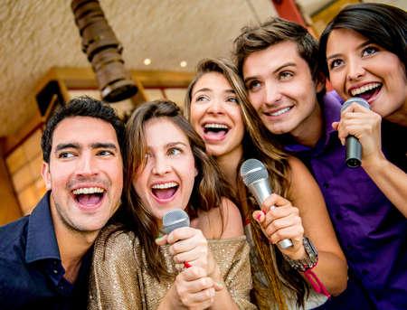 cantando: Feliz grupo de personas cantando karaoke en el bar