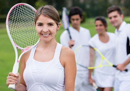 Female tennis player holding racket with her team at the background photo