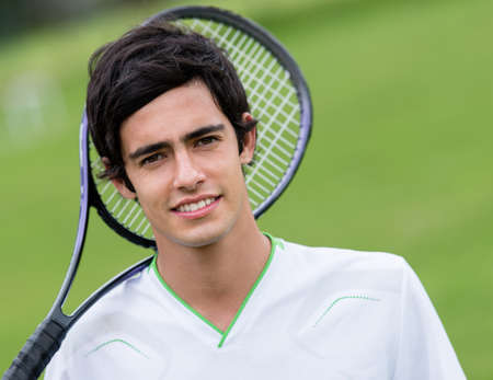 Male tennis player holding racket at the court photo