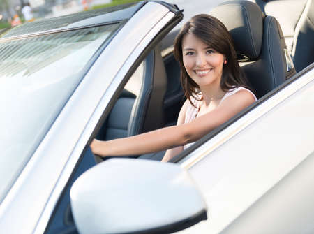 Woman driving a car and looking very happy photo