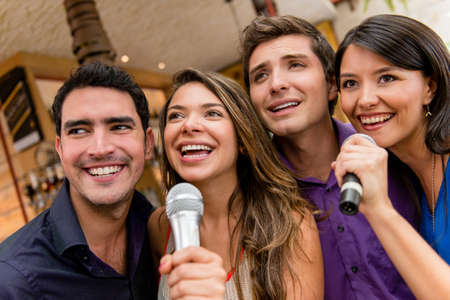 Group of people karaoke singing at the bar having fun photo