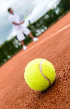 jugando tenis: Partido de tenis en una cancha de arcilla con una pelota que descansa en el lado Foto de archivo