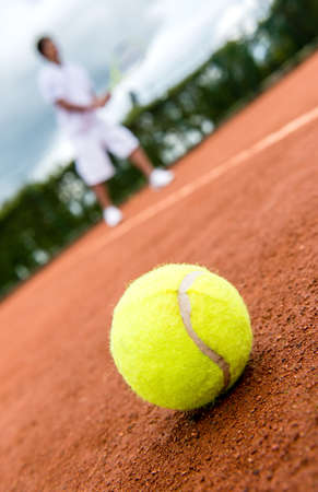 Tennis match at a clay court with a ball lying on the side photo