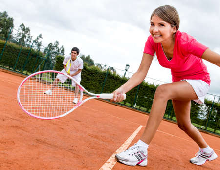 Tennis players playing doubles at a clay court photo