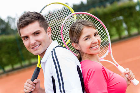 Portrait of a couple playing tennis and holding rackets photo
