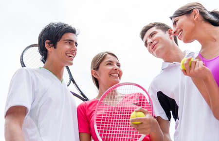 Group of tennis players talking at the court and holding rackets photo