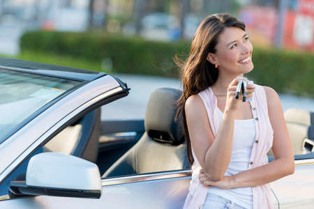 Thoughtful woman holding car keys looking happy Stock Photo - 19425686