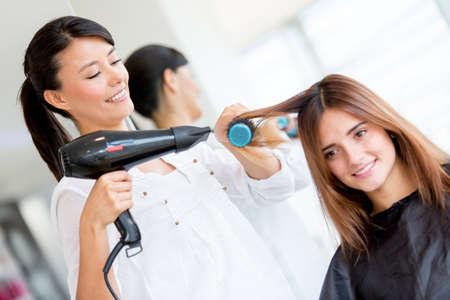 secador de pelo: Mujer con el pelo largo en el sal�n de belleza que consigue un soplador