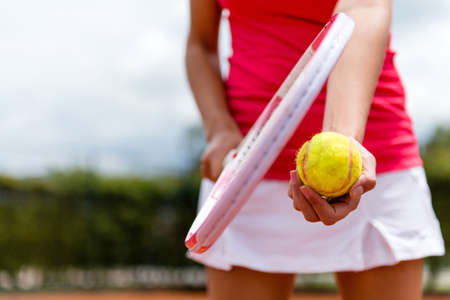 Female tennis player holding racket and a ball photo