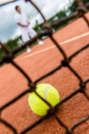 Tennis player playing a match - close up on the net photo