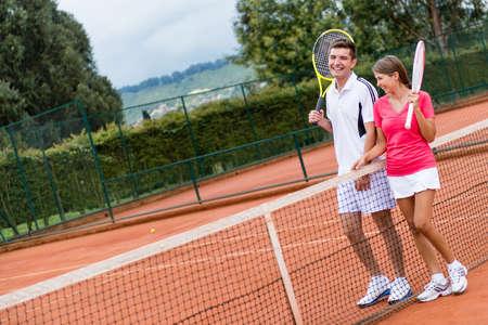 jugando tenis: Un par de jugadores de tenis en la corte y raquetas de celebraci�n