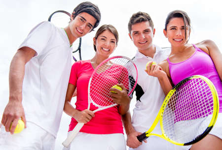 Group of friends playing tennis outdoors and looking very happy photo