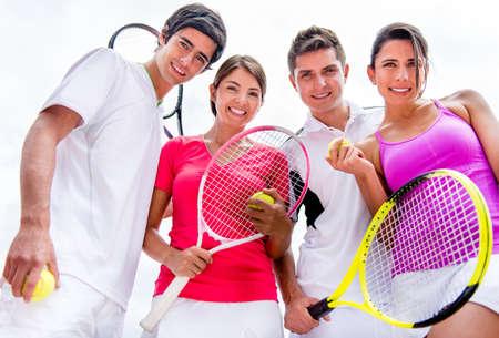 jugando tenis: Grupo de amigos que juegan tenis al aire libre y mirando muy feliz