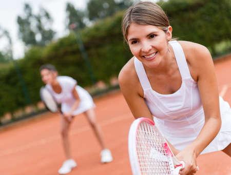 jugando tenis: Tenistas jugando dobles y una mirada feliz