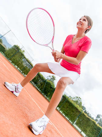 Female tennis player holding racket waiting for a service photo