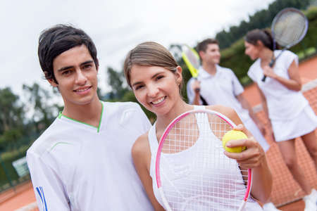 Tennis couple playing doubles at the court looking happy photo