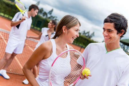 Tennis couple at the court playing doubles and looking happy photo