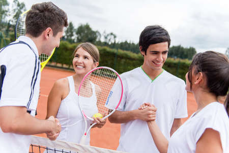 opponents: Group of tennis players giving a handshake after a match