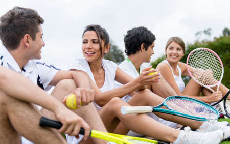 Group of happy tennis players resting outdoors photo