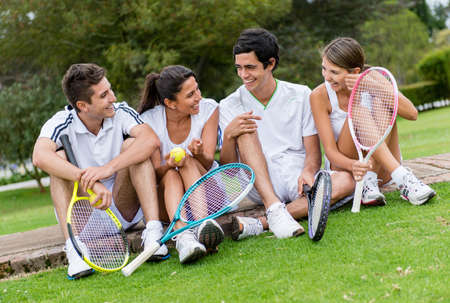 lawn tennis: Group of tennis players talking outdoors looking happy