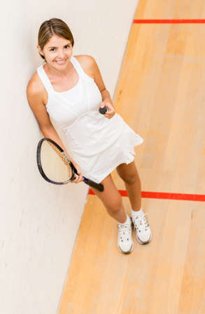 Female player of squash holding racket and ball photo